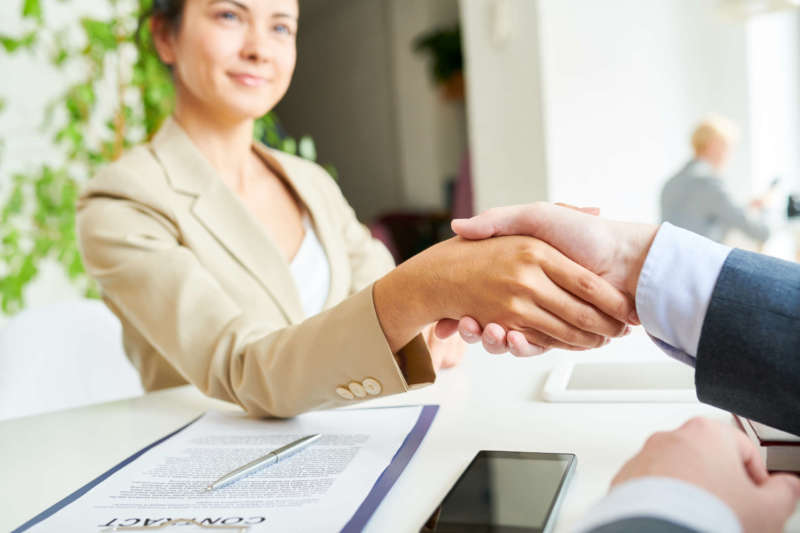 Portrait of pretty female manager shaking hands with client over contract lying on table after negotiations during meeting in office, focus on hands in foreground