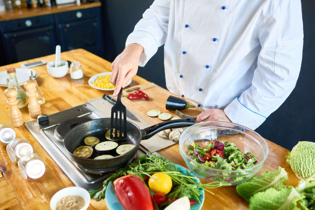 A chef frying eggplant in a pan and preparing a salad.