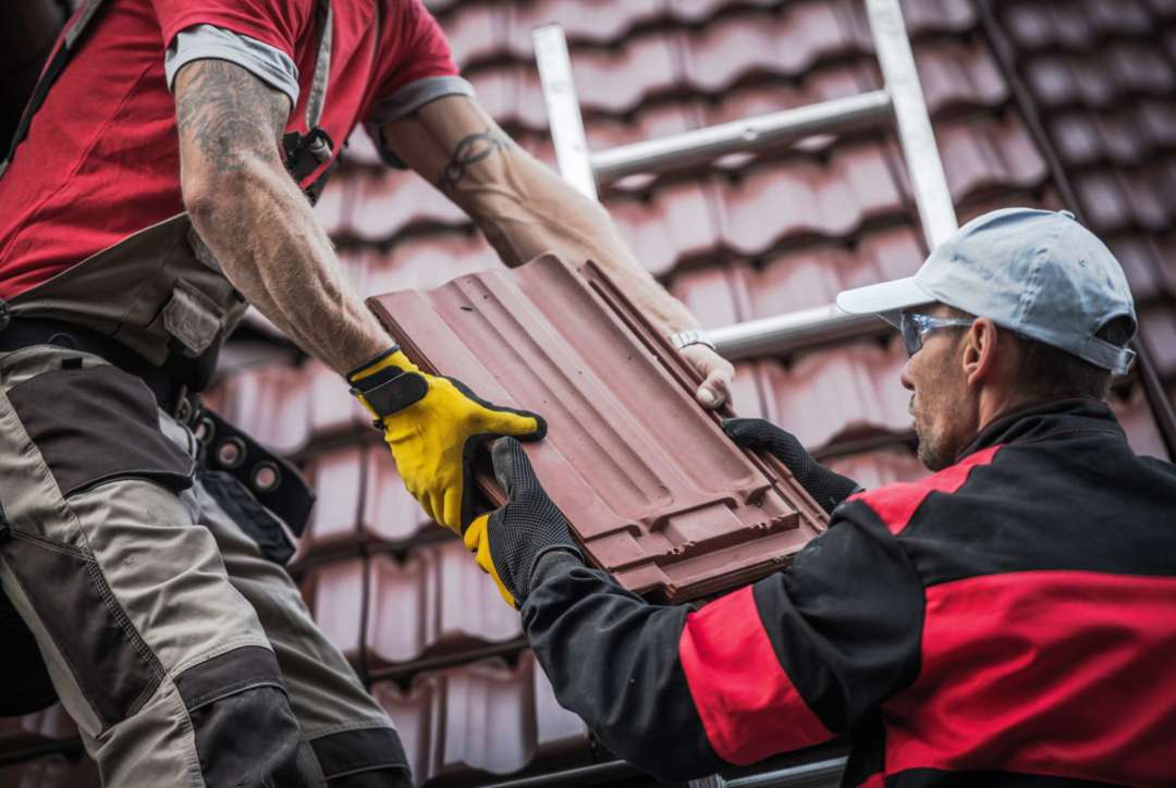 Roofers hand tiles to each other