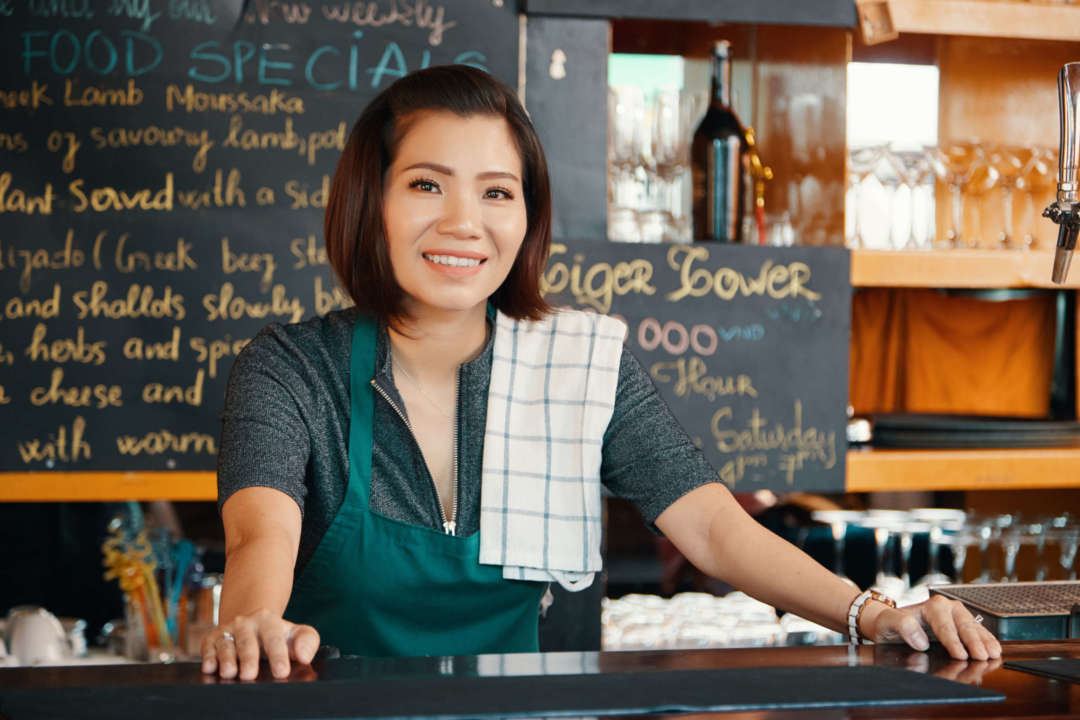 Coffee Shop Owner standing with a smile because she's covered by Fero Insurance.